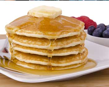 A stack of delicious iHop original buttermilk pancakes topped with butter and syrup.